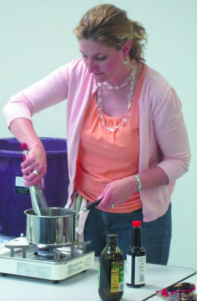 Michelle Moyes Dill from Big Green Tomato prepares noodles during a cooking demonstration at the No More Empty Pots-assisted Tomāto Tomäto CSA program pick-up at the Charles Drew Health Center in Omaha.