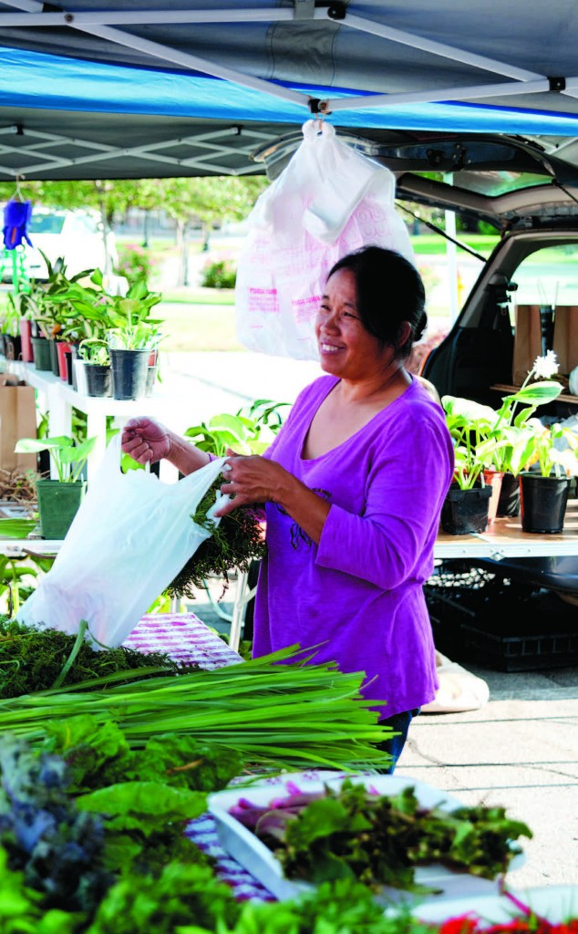 Baskets of Thai eggplant are just some of the unique Asian produce offered. Right: Mai helping customers at Village Pointe's Saturday morning market.