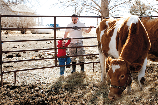 William Powers stresses the importance of building the Nebraska Sustainable Agriculture Society in such a way that it includes families at every stage of life. Here, William and his son, Aiden, check in on the cows