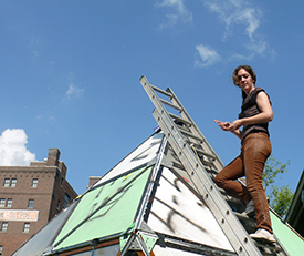 New York City–based Artist Mary Mattingly stands atop a Flock House during the construction process which required the sealing of joints with caulking to keep the units watertight.