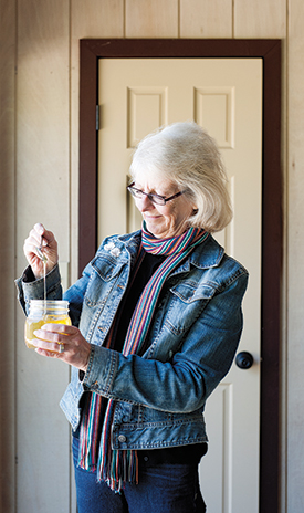 Gayle Duda, owner and operator of a bee farm based in Ponca Hills, Nebraska, spoons up a taste of her homegrown honey.