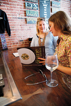 Dana Damewood, Summer Miller's book photographer, and Cindy Driscoll, who assisted with recipe testing and cooking during the photography shoots, thumb through a copy of  New Prairie Kitchen.