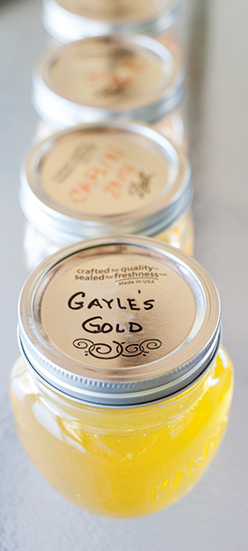 "Jars of ""Gayle's Gold"" honey are lined up in a row, ready for shipment or sale."