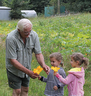 Joe Driscoll shares pumpkin blossoms with two young visitors to the Loess Hills Young People's Farm. The farm is a partnership between Driscoll, longtime owner of the property, and SILT, an organization formed last January with a mission to preserve the health of Iowa's soils. Photo by Laura Low