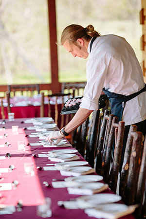 Chef Clayton Chapman of the Grey Plume sets the table at an open-air dinner held at Sawmill Hollow Family Farm.
