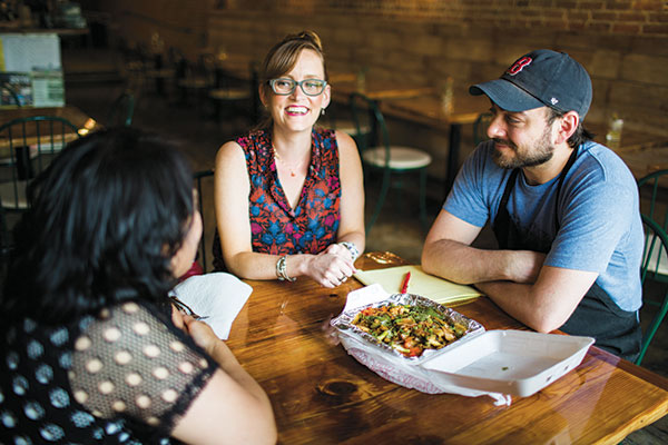 """Kitchen Table co-owners Jessica and Paul Duggan collaborate with Moorah Khin, a Karen refugee from the border area of Burma and Thailand. Together they created a dish centered around her """"food memories."""" (Photo by Bridget McQuillan)"""